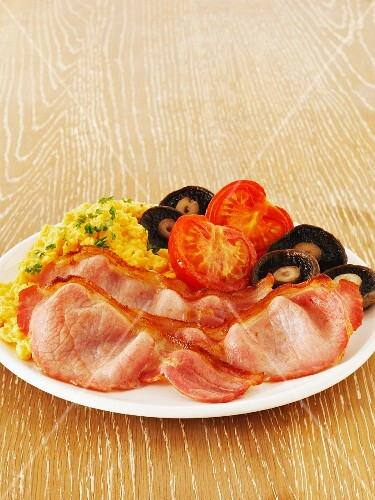 A breakfast platter with bacon, scrambled eggs, mushrooms and tomatoes