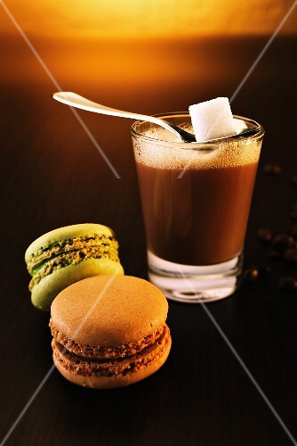 A glass of coffee with a spoon and a sugar cube next to two macaroons