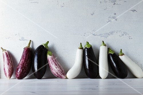 A row of various aubergines (white, purple and stripped)