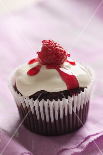 A chocolate and raspberry cupcake topped with cream, raspberry syrup and a fresh raspberry