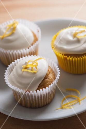 Three lemon cupcakes with cream and lemon zest