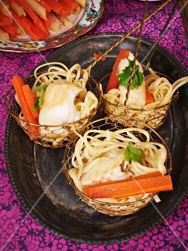 Noodles and fish in hotpot baskets
