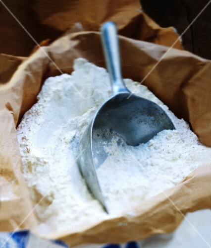 Flour in a paper sack with a scoop