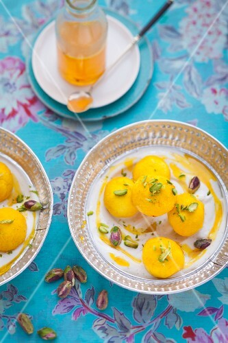Milk balls with saffron in yoghurt with pistachios and sugar syrup