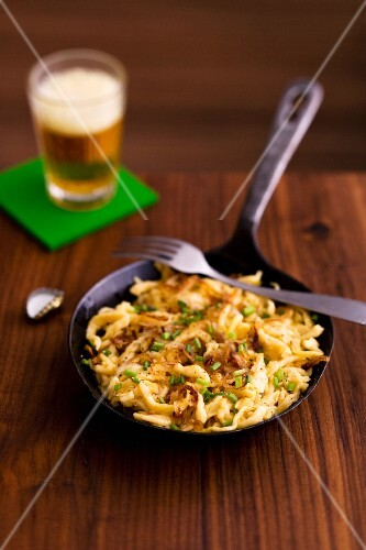 Cheese Spätzle (soft egg noodles from Swabia) in a pan with a glass of beer in the background