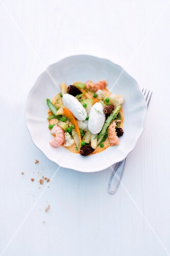 Leipziger Allerlei (regional German vegetable dish consisting of peas, carrots, asparagus, and morel mushrooms) made with scampi