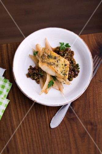 Fish fillet on a bed of black salsify and lentils