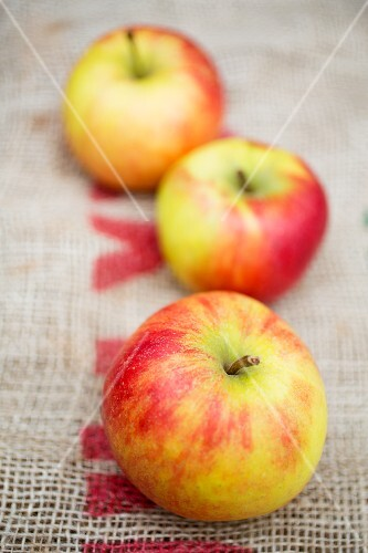 Three fresh apples on a piece of jute