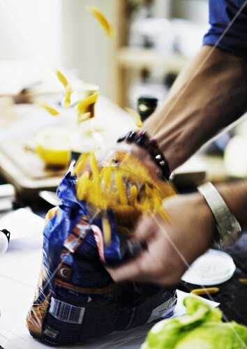 A packet of pasta being opened