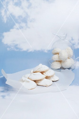 Meringues on a piece of paper and under a glass cloche