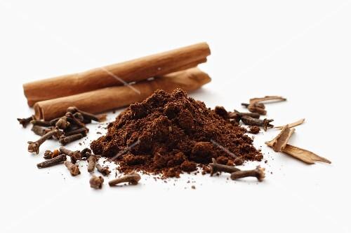 Coffee powder on a metal scoop between cinnamon sticks and cloves