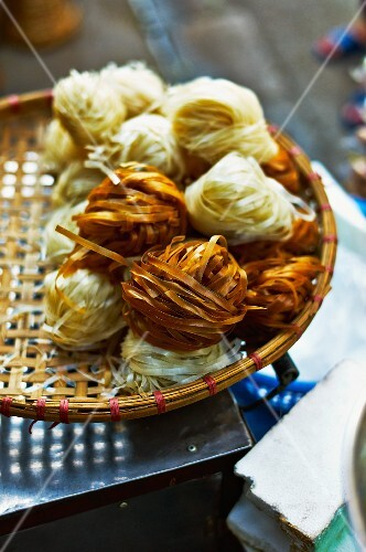 Noodle nests made from light and dark rice noodles at a market in Haiphong, Vietnam
