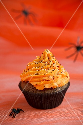 A chocolate cupcake topped with orange buttercream for Halloween