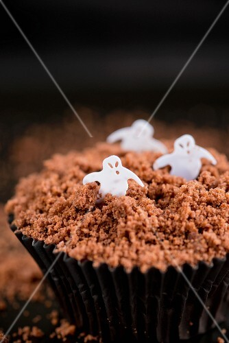 A chocolate cupcake decorated with ghosts for Halloween