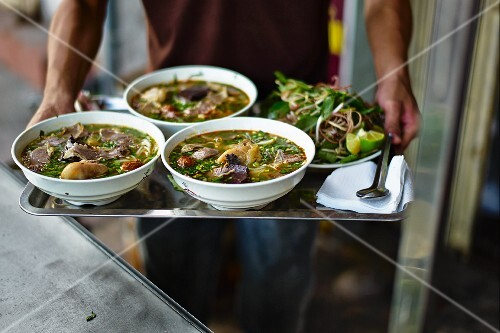 A man holding three bowls of pho ga (Vietnamese chicken soup) on a tray