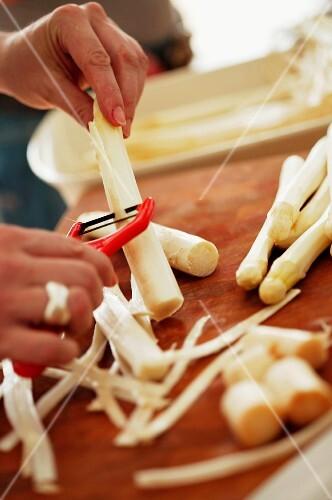 A woman peeling white asparagus