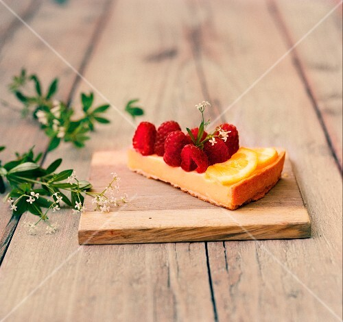A slice of lemon cream tart with woodruff raspberries