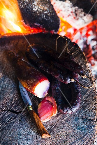 Grilled chorizo on a tree stump next to a camp fire