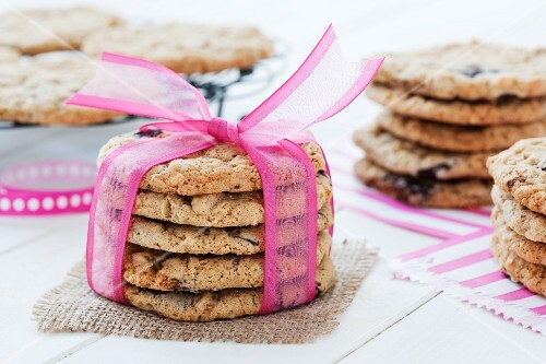 A stack of chocolate chip cookies tied with a pink ribbon