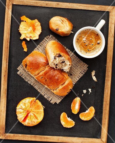 Chocolate chip brioche rolls, coffee and mandarins served on a blackboard