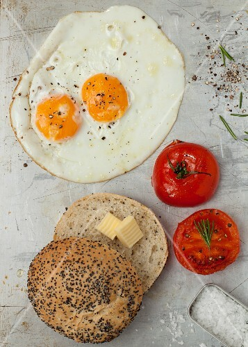 A fried egg with tomatoes and a poppyseed roll with butter