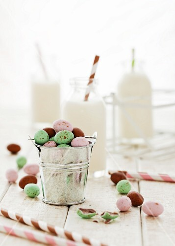 A mini bucket of pastel coloured chocolate eggs with small bottles of milk in the background