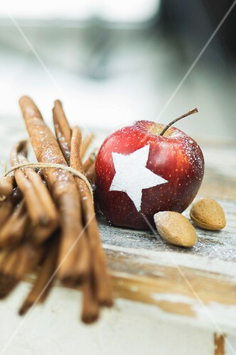 A Christmas apple decorated with a snow star next to cinnamon sticks and almonds on a table