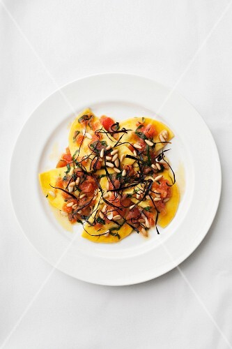 Pumpkin ravioli with tomatoes and pine nuts (seen from above)