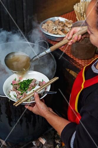 A woman making noodle soup at a market, Laos