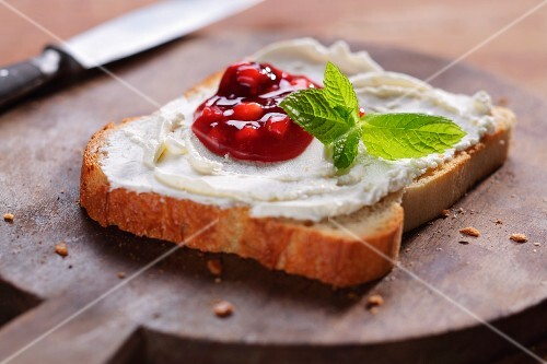 A slice of toast topped with cream cheese and strawberry jam (close-up)