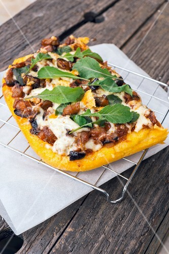 Polenta pizza with caponate, cheese, rocket and basil