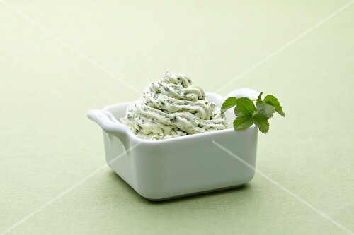 A bowl of herb butter against a white background
