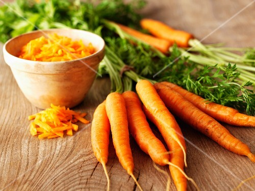 Whole organic carrots and a bowl of grated carrot
