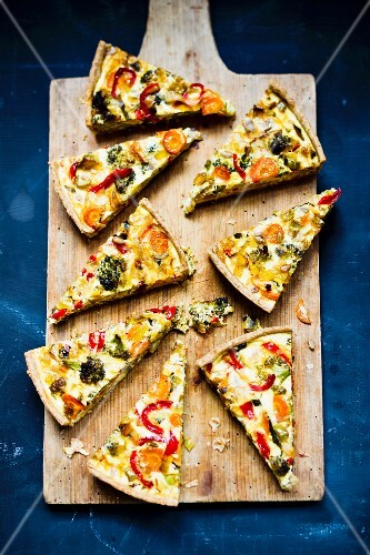 Vegetable quiche, sliced, on a chopping board