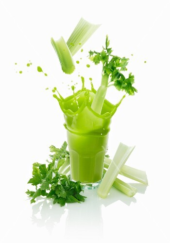 Celery sticks falling into a vegetable drink