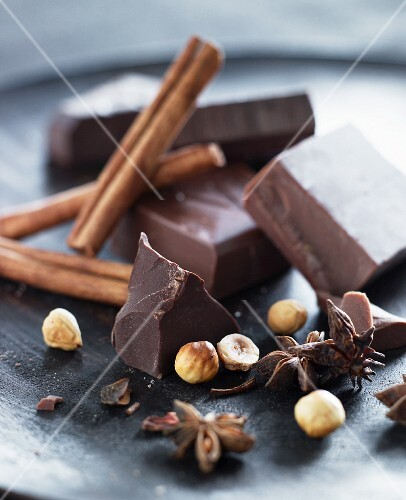 Chocolate, nuts and spice on a black plate