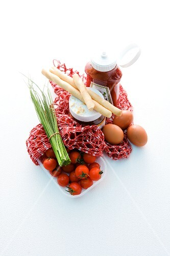 A net shopping bag with tomatoes, chives, bread sticks, eggs and sauces
