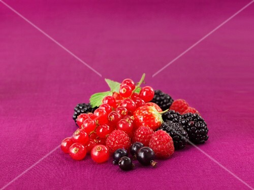 Mixed fresh berries on a purple surface