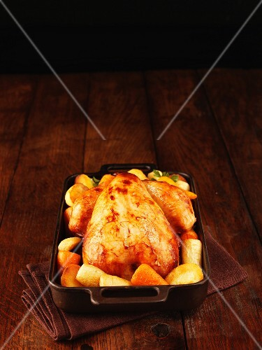 Roast chicken with root vegetables in a roasting tin