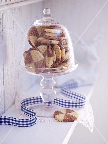 Black and white biscuits under a glass cloche