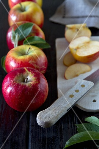 Apples with leaves, sliced on a board with a knife