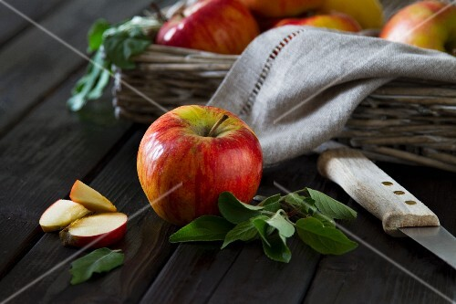 An apple with leaves in front of an apple basket with a few pieces of apple next to it