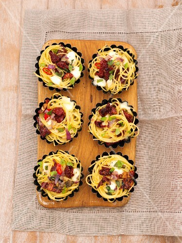 Gratinated spaghetti nests with bacon and dried tomatoes