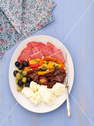 An appetiser platter featuring mozzarella, olives, tomatoes, peppers and sausage