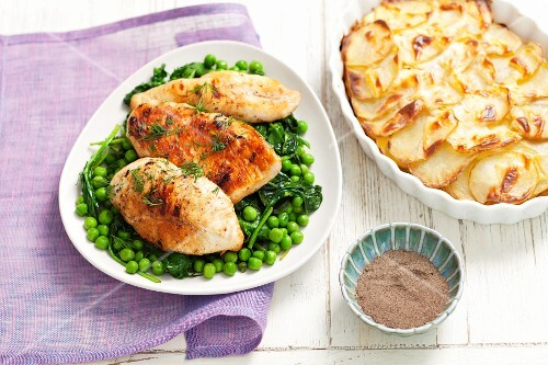 Chicken breast on a bed of peas and spinach served with potato gratin