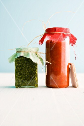 Sweet and spicy pepper and tomato sugo next to basil and lemon pesto