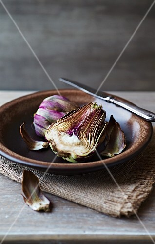 A halved artichoke on a ceramic plate