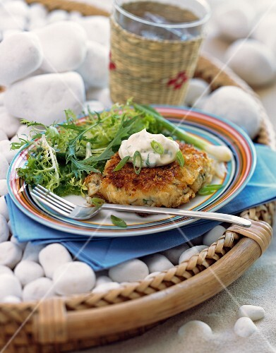 A crabcake and salad on a plate on the beach