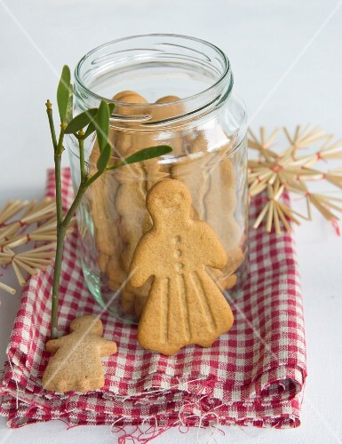 A jar of gingerbread on a cloth with mistletoe and straw stars