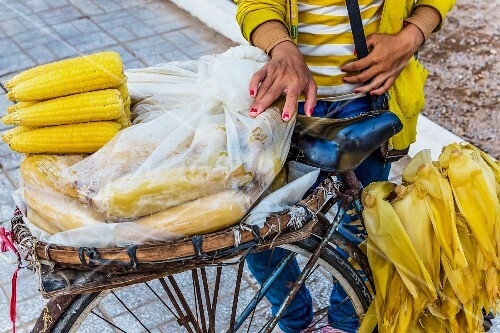 A mobile vendor selling corn cobs at a market in Phnom Penh, Cambodia